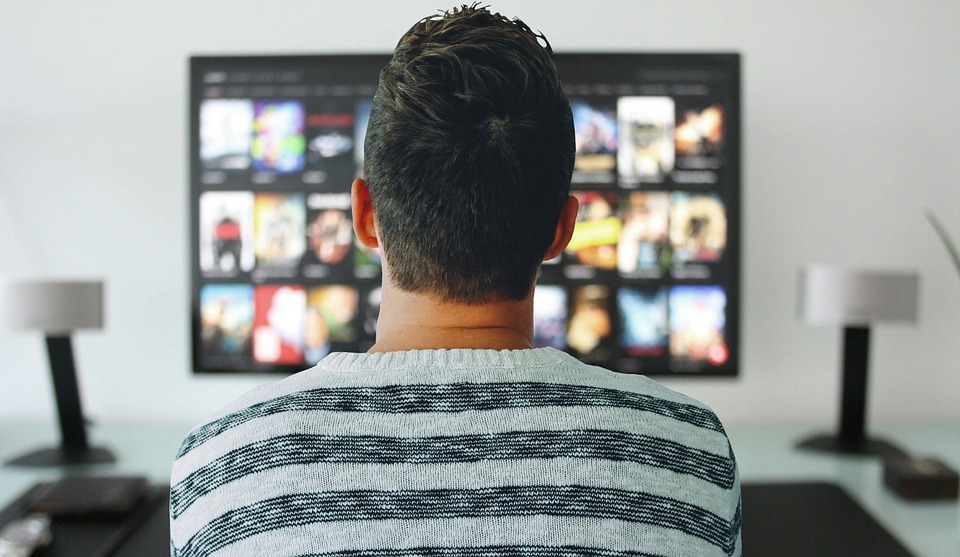 A photo of a man watching TV